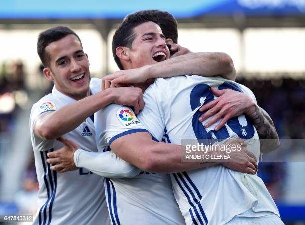 Real Madrid's midfielder Marco Asensio Willemsen celebrates with teammates forward Lucas Vazquez and Colombian midfielder James Rodriguez after...