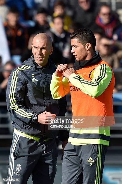 Real Madrid's new French coach Zinedine Zidane and Real Madrid's Portuguese forward Cristiano Ronaldo gesture during his first training session as...