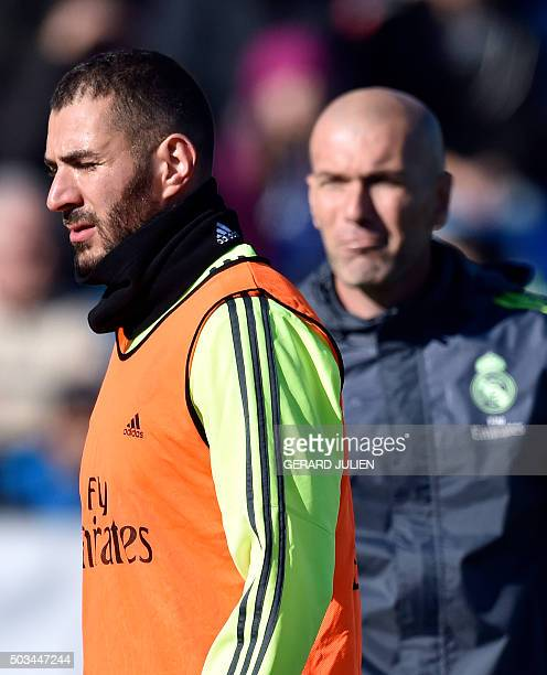 Real Madrid's new French coach Zinedine Zidane looks at Real Madrid's French forward Karim Benzema during his first training session as coach of Real...