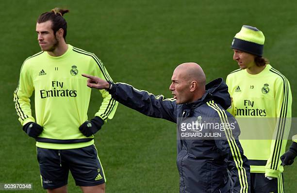 Real Madrid's new French coach Zinedine Zidane points his finger next to Real Madrid's Welsh forward Gareth Bale and Real Madrid's Croatian...