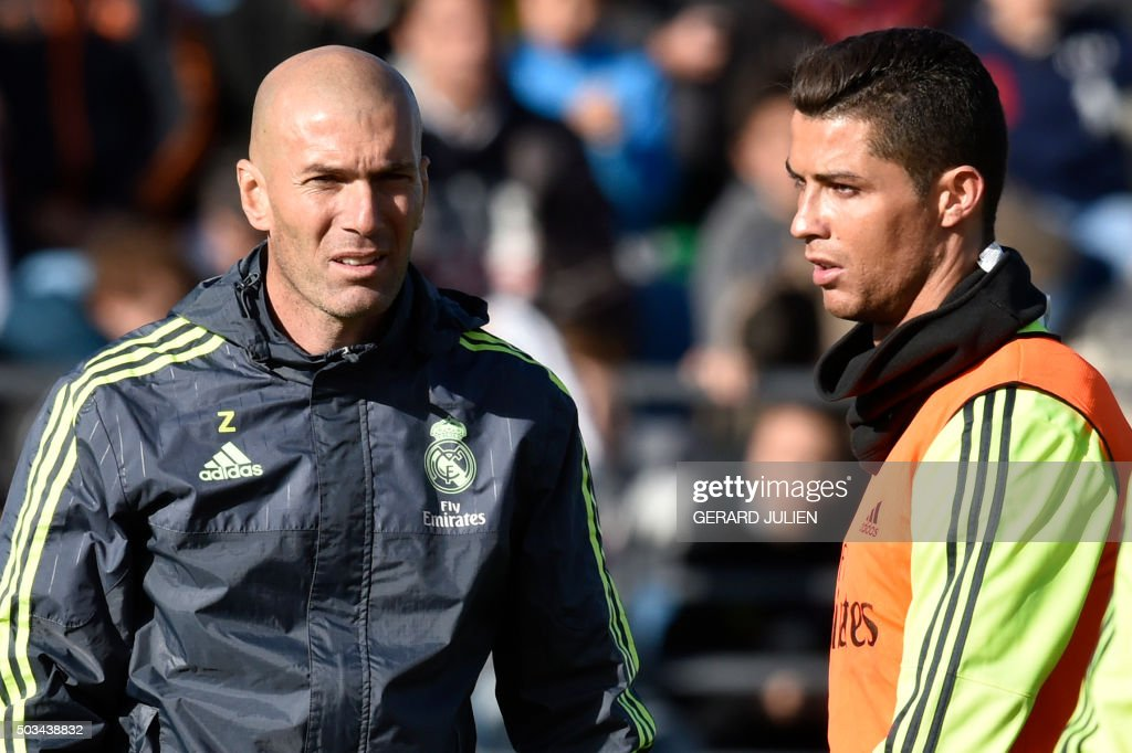 TOPSHOT - Real Madrid's new French coach Zinedine Zidane (L) walks past Real Madrid's Portuguese forward Cristiano Ronaldo during his first training session as coach of Real Madrid at the Alfredo di Stefano stadium in Valdebebas, on the outskirts of Madrid, on January 5, 2016. Real Madrid legend Zinedine Zidane promised to put his 'heart and soul' into managing the Spanish giants after he was sensationally named as coach following Rafael Benitez's unceremonious sacking.