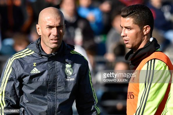 TOPSHOT Real Madrid's new French coach Zinedine Zidane walks past Real Madrid's Portuguese forward Cristiano Ronaldo during his first training...