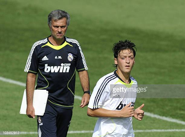 Real Madrid's new German midfielder Mesut Ozil and coach Jose Mourinho attend a training session at the Real Madrid sport city in Madrid on August 19...