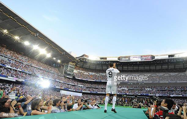 Real Madrid's new player Portuguese Cristiano Ronaldo applauds during his official presentation at the Santiago Bernabeu stadium in Madrid on July 6...