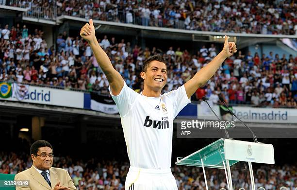 Real Madrid's new player Portuguese Cristiano Ronaldo waves to supporters next to former football player Portuguese Eusebio during his official...