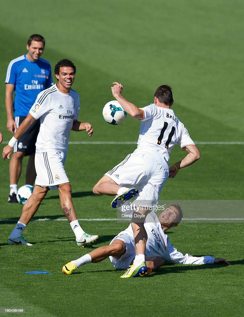 Real Madrid's new signing <a gi-track='captionPersonalityLinkClicked' href=/galleries/search?phrase=Gareth+Bale&family=editorial&specificpeople=609290 ng-click='$event.stopPropagation()'>Gareth Bale</a> (#11) is tackled by <a gi-track='captionPersonalityLinkClicked' href=/galleries/search?phrase=Cristiano+Ronaldo+-+Soccer+Player&family=editorial&specificpeople=162689 ng-click='$event.stopPropagation()'>Cristiano Ronaldo</a> while teammate Pepe looks on during a team training session on September 13, 2013 in Madrid, Spain.