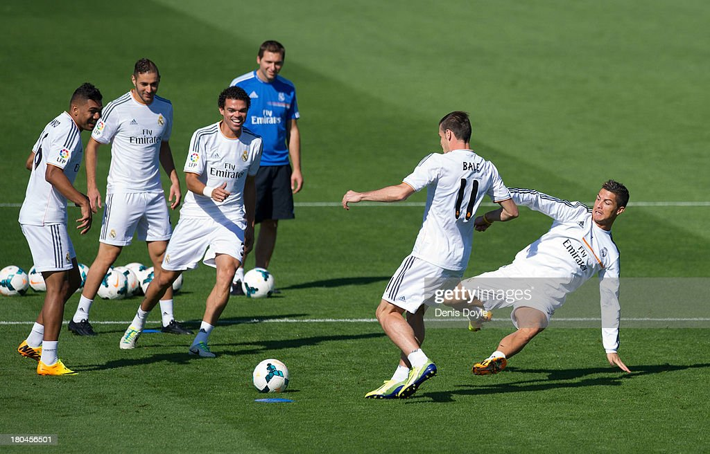 Real Madrid's new signing <a gi-track='captionPersonalityLinkClicked' href=/galleries/search?phrase=Gareth+Bale&family=editorial&specificpeople=609290 ng-click='$event.stopPropagation()'>Gareth Bale</a> (#11) is tackled by <a gi-track='captionPersonalityLinkClicked' href=/galleries/search?phrase=Cristiano+Ronaldo+-+Soccer+Player&family=editorial&specificpeople=162689 ng-click='$event.stopPropagation()'>Cristiano Ronaldo</a> while teammates Jese Rodriguez (L), <a gi-track='captionPersonalityLinkClicked' href=/galleries/search?phrase=Karim+Benzema&family=editorial&specificpeople=796089 ng-click='$event.stopPropagation()'>Karim Benzema</a> (2.L), Pepe and assistant coach <a gi-track='captionPersonalityLinkClicked' href=/galleries/search?phrase=Zinedine+Zidane&family=editorial&specificpeople=172012 ng-click='$event.stopPropagation()'>Zinedine Zidane</a> look on during a team training session on September 13, 2013 in Madrid, Spain.