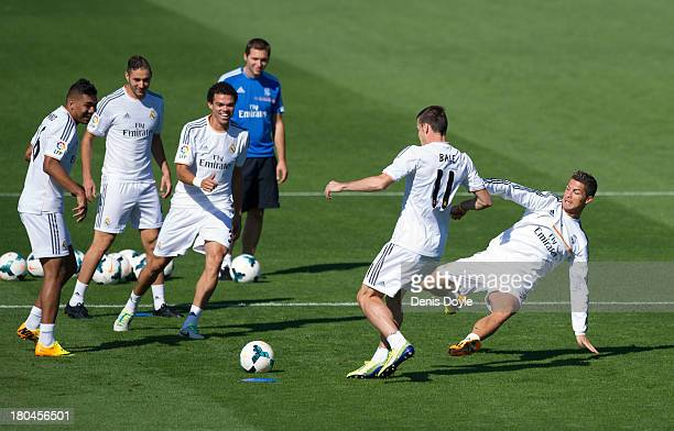 Real Madrid's new signing Gareth Bale is tackled by Cristiano Ronaldo while teammates Jese Rodriguez Karim Benzema Pepe and assistant coach Zinedine...