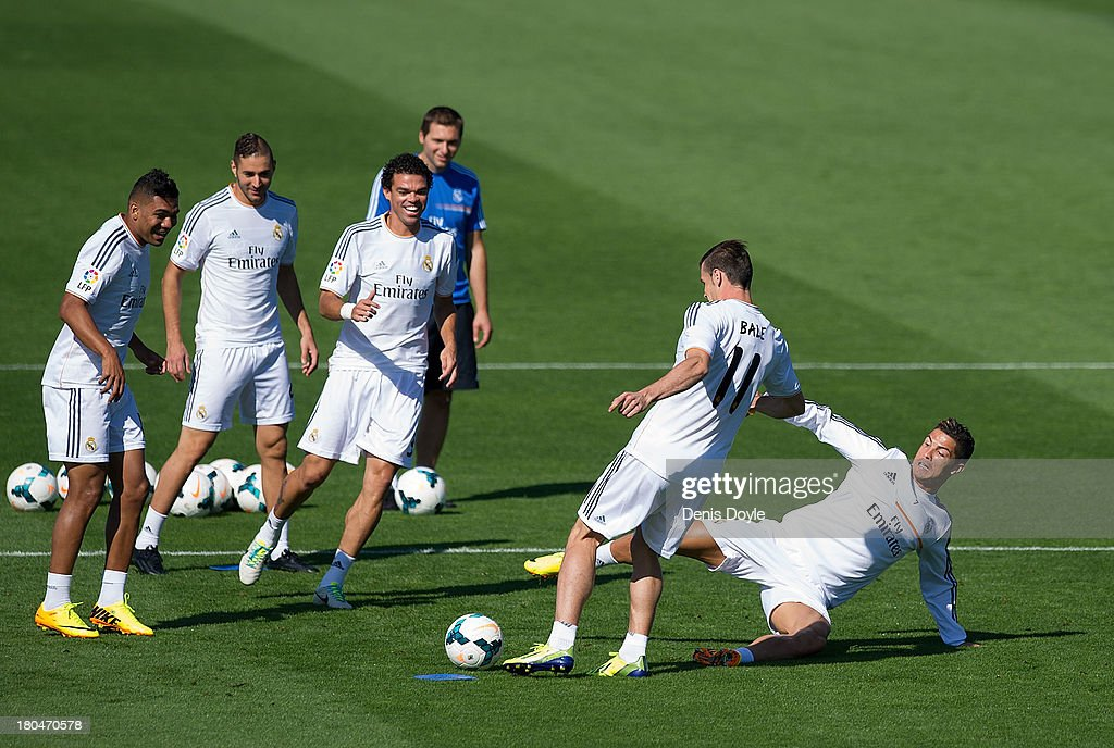 Real Madrid's new signing <a gi-track='captionPersonalityLinkClicked' href=/galleries/search?phrase=Gareth+Bale&family=editorial&specificpeople=609290 ng-click='$event.stopPropagation()'>Gareth Bale</a> (#11) is tackled by <a gi-track='captionPersonalityLinkClicked' href=/galleries/search?phrase=Cristiano+Ronaldo+-+Soccer+Player&family=editorial&specificpeople=162689 ng-click='$event.stopPropagation()'>Cristiano Ronaldo</a> while team mates Jese Rodriguez (L), <a gi-track='captionPersonalityLinkClicked' href=/galleries/search?phrase=Karim+Benzema&family=editorial&specificpeople=796089 ng-click='$event.stopPropagation()'>Karim Benzema</a> (2L), Pepe and assistant coach <a gi-track='captionPersonalityLinkClicked' href=/galleries/search?phrase=Zinedine+Zidane&family=editorial&specificpeople=172012 ng-click='$event.stopPropagation()'>Zinedine Zidane</a> look on during a team training session on September 13, 2013 in Madrid, Spain.