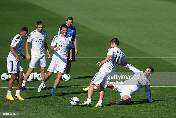 Real Madrid's new signing Gareth Bale is tackled by Cristiano Ronaldo while team mates Jese Rodriguez Karim Benzema Pepe and assistant coach Zinedine...