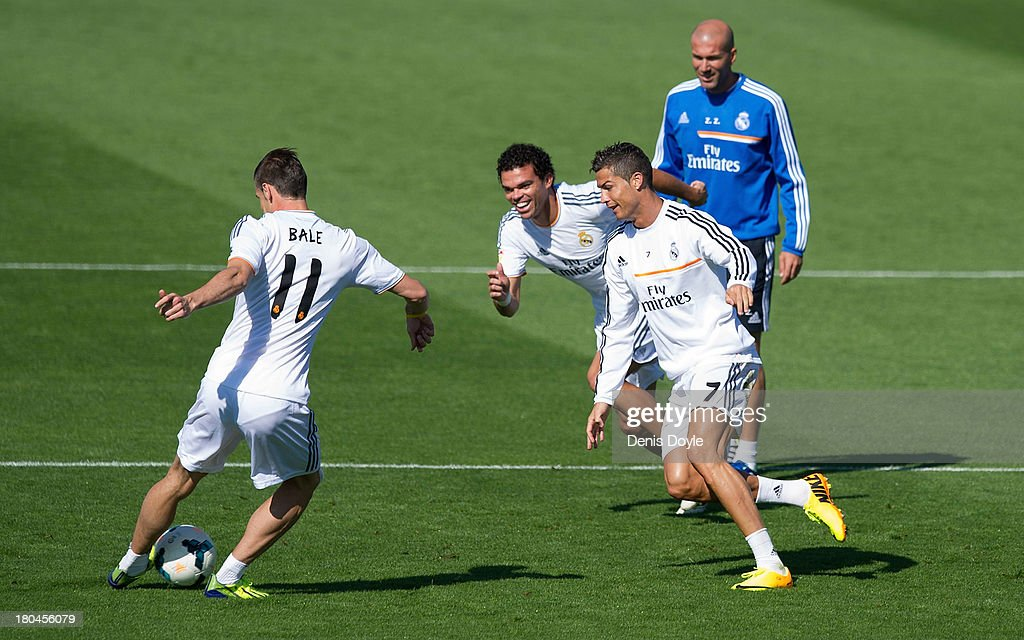 Real Madrid's new signing Gareth Bale (#11) passes the ball past Cristiano Ronaldo (R) and Pepe (C) while assistant coach Zinedine Zidane looks on during a team training session on September 13, 2013 in Madrid, Spain.