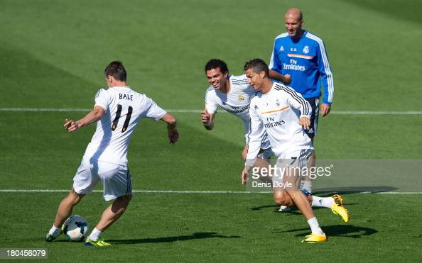 Real Madrid's new signing Gareth Bale passes the ball past Cristiano Ronaldo and Pepe while assistant coach Zinedine Zidane looks on during a team...