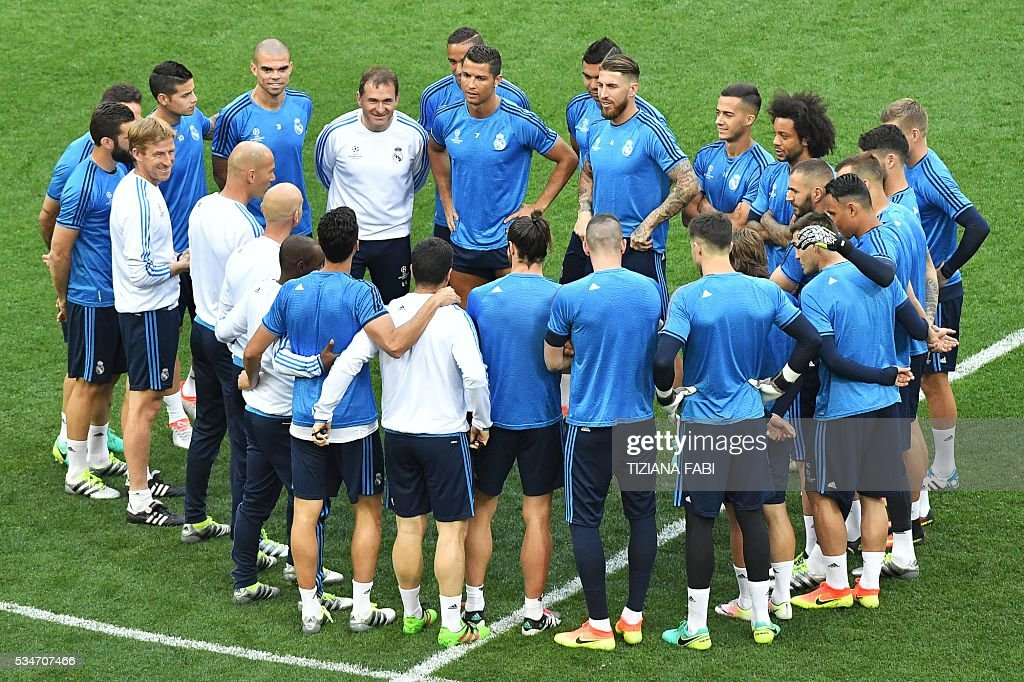 Real Madrid's players gather to listen to their French coach Zinedine Zidane (4th L) at the start of a training session at the San Siro Stadium in Milan, on May 27, 2016, on the eve of the UEFA Champions League final foobtall match between Real Madrid and Atletico Madrid. / AFP / TIZIANA