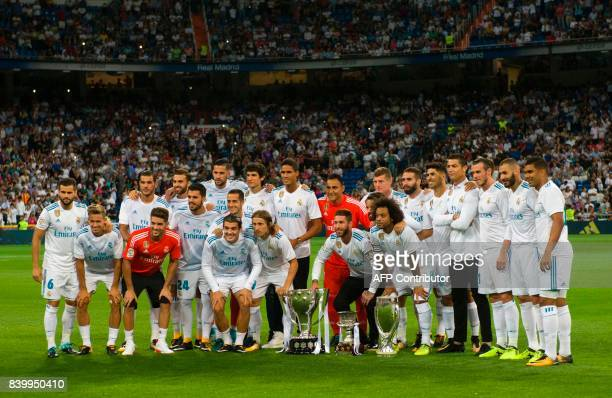 Real Madrid's players pose with the Spanish Supercup the Europe Super cup and the Spanish League cup before the Spanish league football match Real...