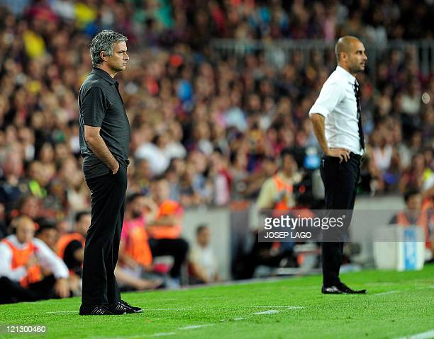 Real Madrid's Portuguese coach Jose Mourinho and Barcelona's coach Josep Guardiola look on during the second leg of the Spanish Supercup football...