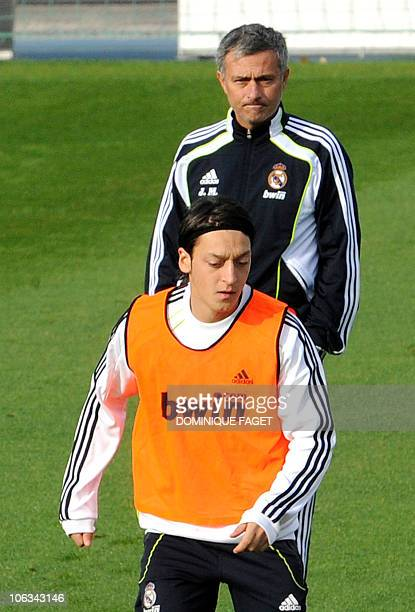 Real Madrid's Portuguese coach Jose Mourinho and German midfielder Mesut Ozil take in a training session at Real Madrid's sport city on October 29...