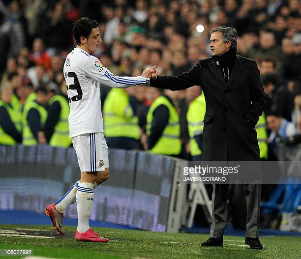Real Madrid's Portuguese coach Jose Mourinho congratulates Real Madrid's German midfielder Mesut Ozil during the Copa del Rey football match Real...