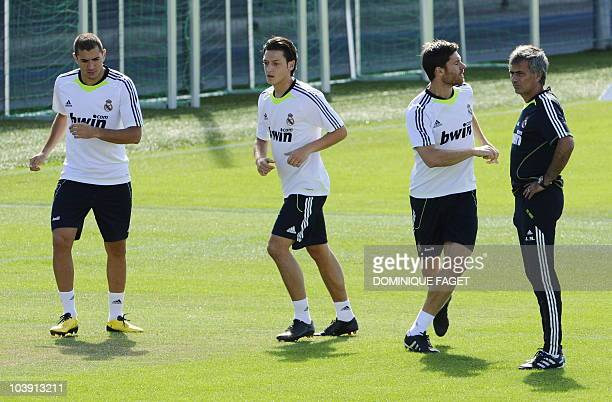 Real Madrid's Portuguese coach Jose Mourinho look at his players French forward Karim Benzema midfielder Xabi Alonso and German midfielder Mesut Ozil...