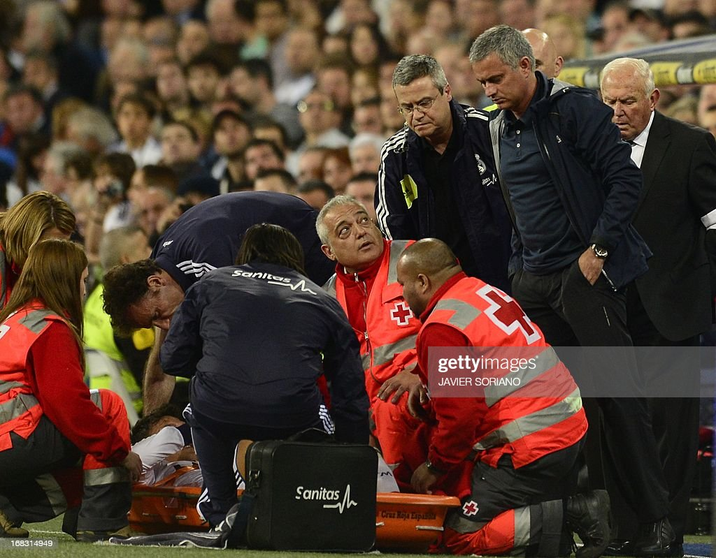 Real Madrid's Portuguese coach Jose Mourinho (R) looks at Real Madrid's German midfielder Mesut Ozil lying on a stretcher during the Spanish league football match Real Madrid CF vs Malaga CF at the Santiago Bernabeu stadium in Madrid on May 8, 2013.