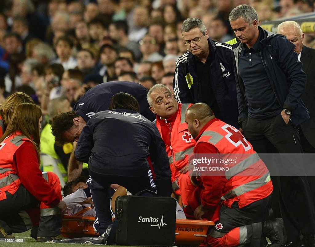 Real Madrid's Portuguese coach Jose Mourinho (R) looks at Real Madrid's German midfielder Mesut Ozil lying on a stretcher during the Spanish league football match Real Madrid CF vs Malaga CF at the Santiago Bernabeu stadium in Madrid on May 8, 2013. AFP PHOTO/ JAVIER SORIANO