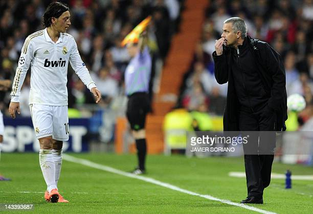 Real Madrid's Portuguese coach Jose Mourinho speaks with Real Madrid's German midfielder Mesut Ozil during the UEFA Champions League second leg...