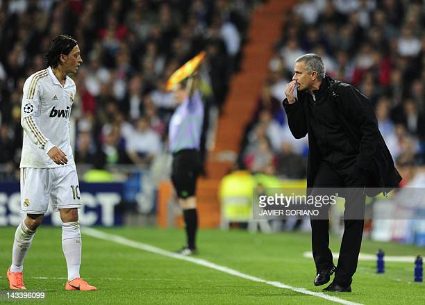 Real Madrid's Portuguese coach Jose Mourinho talks to Real Madrid's German midfielder Mesut Ozil during the UEFA Champions League second leg...