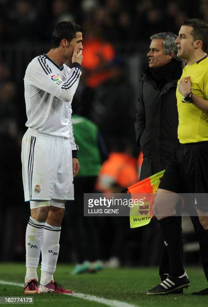 Real Madrid's Portuguese coach Jose Mourinho talks with Real Madrid's Portuguese forward Cristiano Ronaldo during the Spanish Cup semifinal second...
