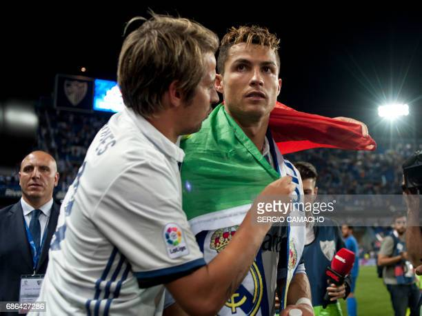 Real Madrid's Portuguese defender Fabio Coentrao wraps Real Madrid's Portuguese forward Cristiano Ronaldo with a Portuguese flag as they celebrate at...