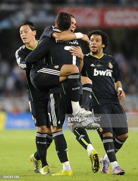 Real Madrid's Portuguese defender Pepe celebrates with teammate Portuguese forward Cristiano Ronaldo after scoring thanks to a kick from Ronaldo...