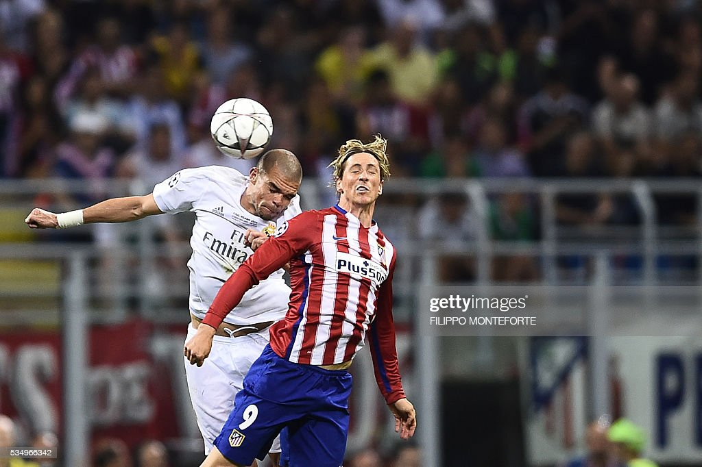 Real Madrid's Portuguese defender Pepe (L) heads the ball next to Atletico Madrid's Spanish forward Fernando Torres during the UEFA Champions League final football match between Real Madrid and Atletico Madrid at San Siro Stadium in Milan, on May 28, 2016. / AFP / FILIPPO