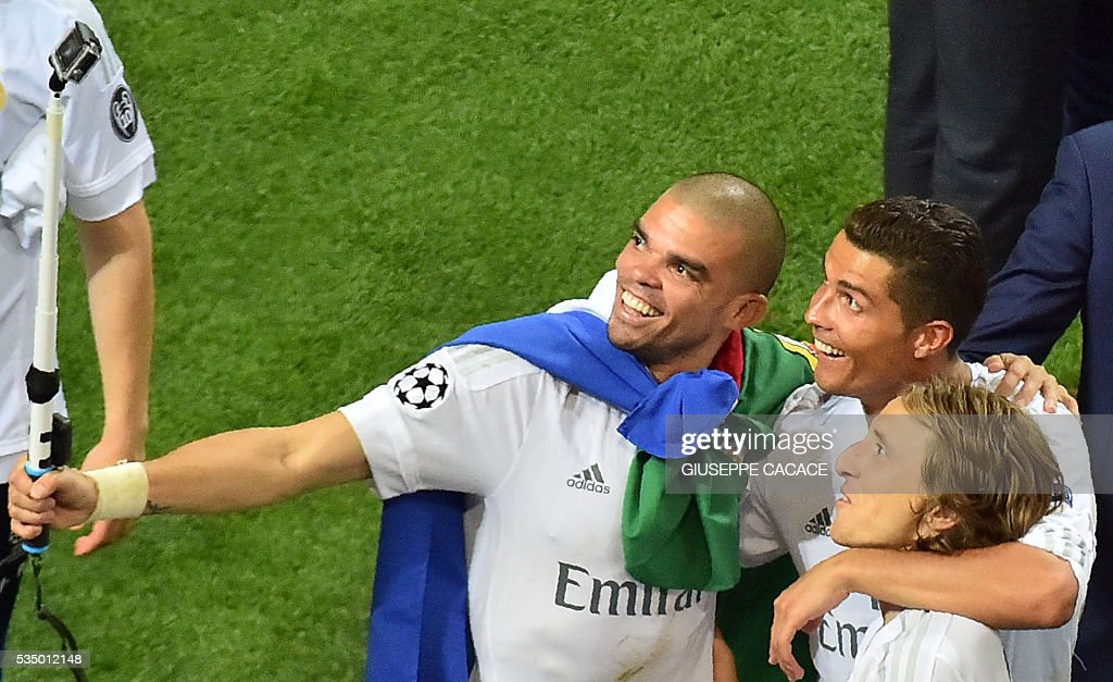 Real Madrid's Portuguese defender Pepe, Portuguese forward Cristiano Ronaldo and Real Madrid's Croatian midfielder Luka Modric pose for a selfie as they celebrate after Real Madrid won the UEFA Champions League final football match over Atletico Madrid at San Siro Stadium in Milan, on May 28, 2016. Real Madrid beat city rivals Atletico for the second time in three years to win the Champions League for the 11th time. / AFP / GIUSEPPE