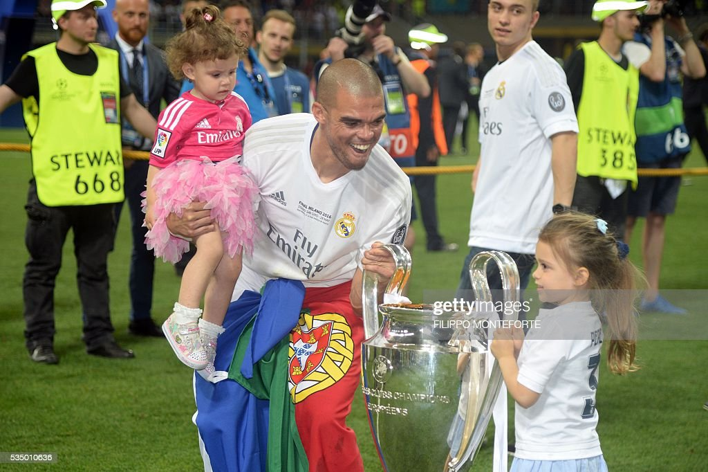 Real Madrid's Portuguese defender Pepe poses with the trophy and his daughters after Real Madrid won the UEFA Champions League final football match between Real Madrid and Atletico Madrid at San Siro Stadium in Milan, on May 28, 2016. / AFP / Filippo MONTEFORTE