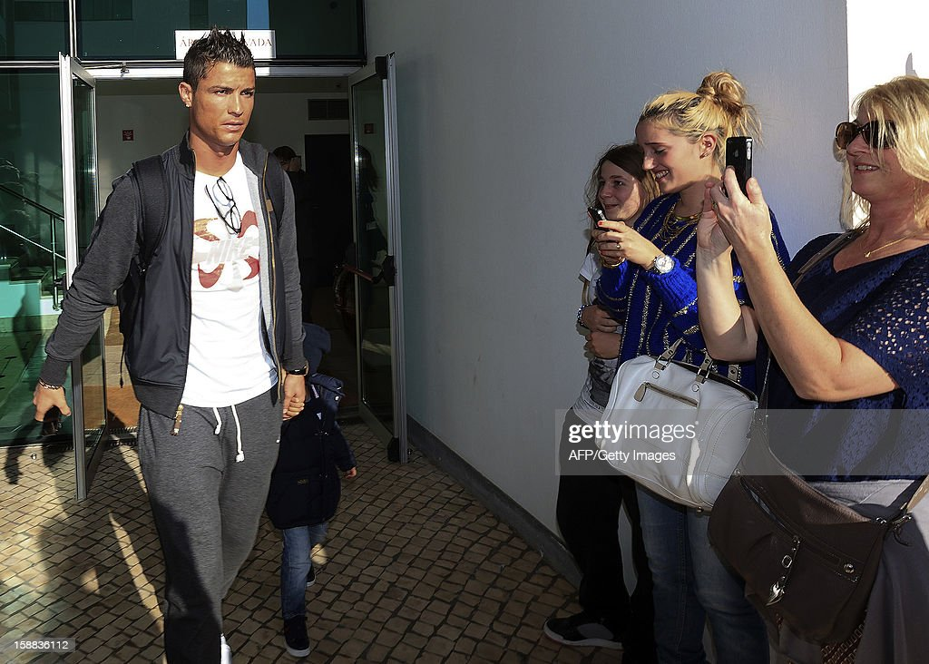 Real Madrid's Portuguese forward Cristiano Ronaldo (L) and his son arrive at Madeira airport in Funchal on December 31, 2012.