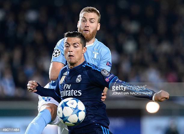 Real Madrid's Portuguese forward Cristiano Ronaldo and Malmo's Norwegian midfielder Jo Inge Berget vie for the ball during the UEFA Champions League...