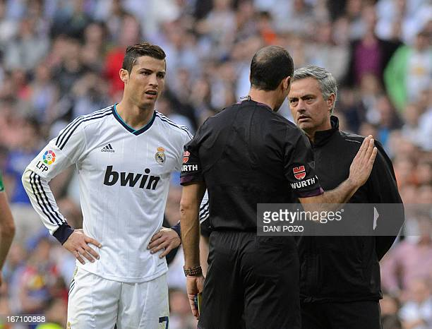 Real Madrid's Portuguese forward Cristiano Ronaldo and Real Madrid's Portuguese coach Jose Mourinho argue with the referee during the Spanish league...