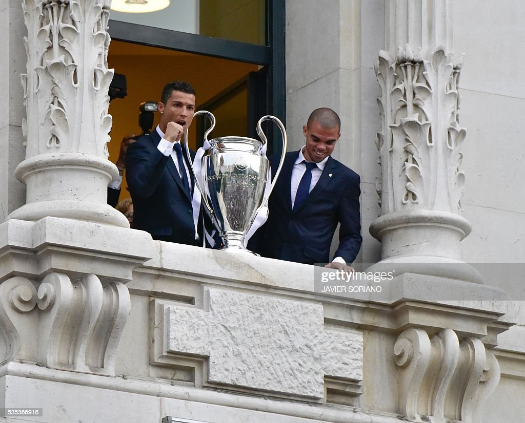 Real Madrid's Portuguese forward Cristiano Ronaldo (L) and Real Madrid's Portuguese defender Pepe show the trophy from Madrid town hall's balcony on May 29, 2016 the day after winning the UEFA Champions League final foobtall match against Club Atletico de Madrid, held in Milan, Italy on May 28, 2016. / AFP / JAVIER