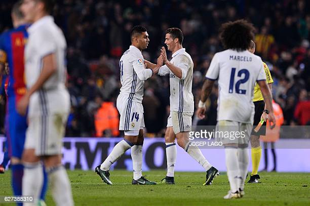 Real Madrid's Portuguese forward Cristiano Ronaldo and Real Madrid's Brazilian midfielder Casemiro celebrate their 11 draw at the end of the Spanish...