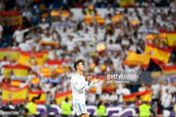 Real Madrid's Portuguese forward Cristiano Ronaldo applauds as Real Madrid's fans cheer with Spanish flags before the Spanish league football match...