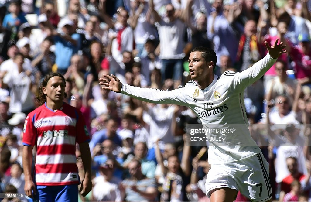 Real Madrid's Portuguese forward Cristiano Ronaldo celebrates a goal past Granada's Chilean midfielder Manuel Rolando Iturra during the Spanish...