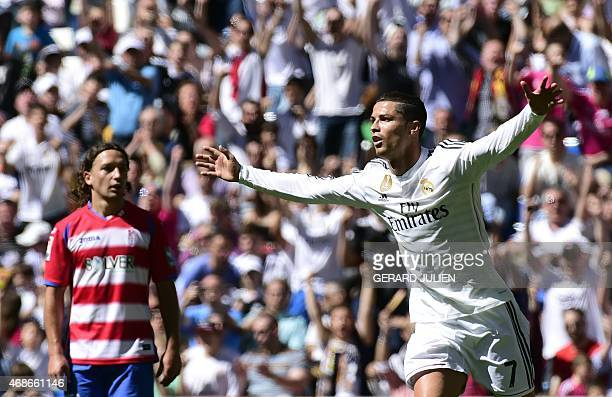 Real Madrid's Portuguese forward Cristiano Ronaldo celebrates a goal past Granada's Chilean midfielder Manuel Rolando Iturra during the Spanish...