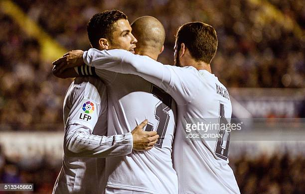 Real Madrid's Portuguese forward Cristiano Ronaldo celebrates a goal with teammates during the Spanish league football match Levante UD vs Real...
