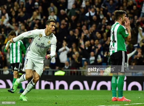 Real Madrid's Portuguese forward Cristiano Ronaldo celebrates after scoring a goal beside Betis' Romanian midfielder Alin Tosca during the Spanish...