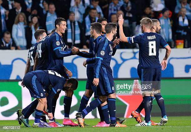 Real Madrid's Portuguese forward Cristiano Ronaldo celebrates after scoring the opening goal with his teammates during the UEFA Champions League...