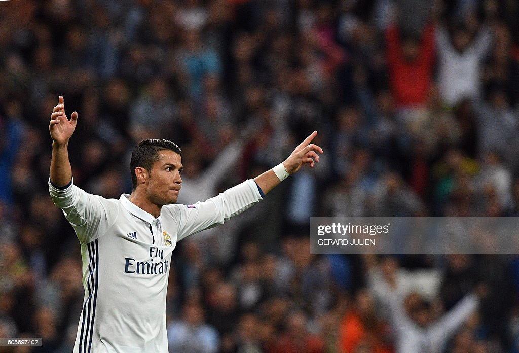 Real Madrid's Portuguese forward Cristiano Ronaldo celebrates after scoring the equalizer during the UEFA Champions League football match Real Madrid CF vs Sporting CP at the Santiago Bernabeu stadium in Madrid on September 14, 2016. / AFP / GERARD