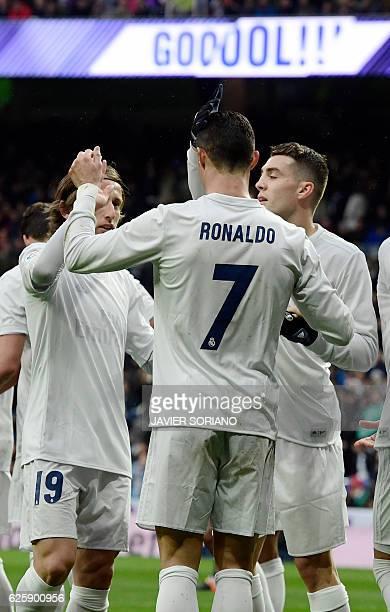 Real Madrid's Portuguese forward Cristiano Ronaldo celebrates his second goal with teammates Real Madrid's Croatian midfielder Luka Modric and Real...