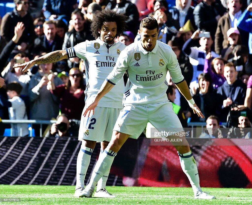 Real Madrid's Portuguese forward Cristiano Ronaldo (front) celebrates past Real Madrid's Brazilian defender Marcelo after scoring during the Spanish league football match Real Madrid CF vs Granada FC at the Santiago Bernabeu stadium in Madrid on January 7, 2017. / AFP / GERARD