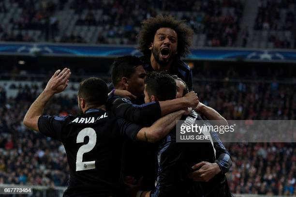 Real Madrid's Portuguese forward Cristiano Ronaldo celebrates scoring the 11 goal with his teammates during the UEFA Champions League 1st leg...