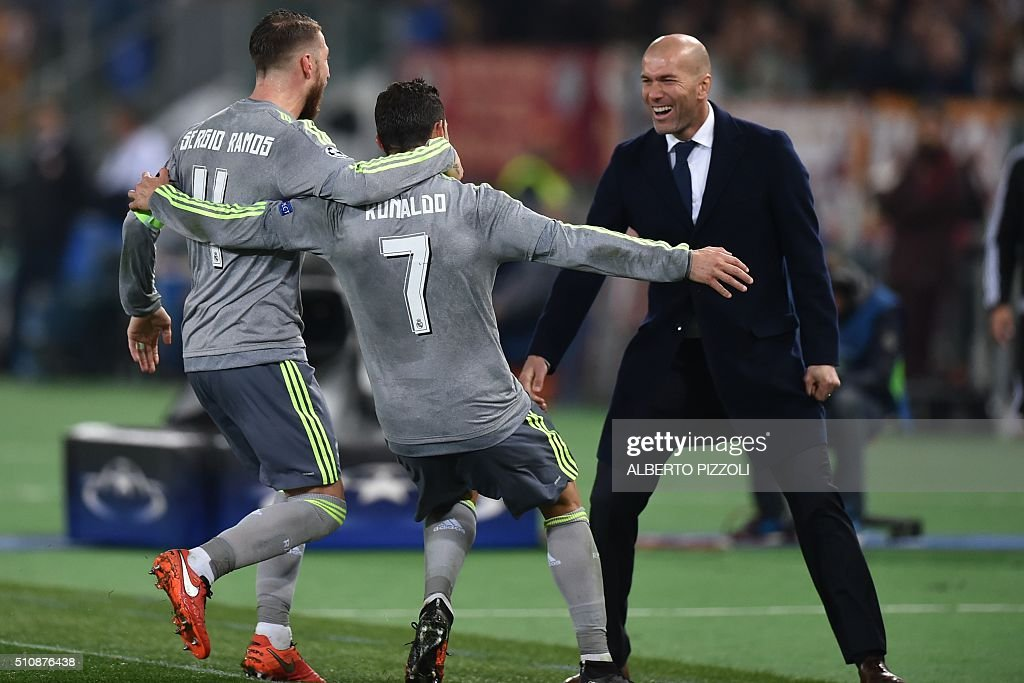 Real Madrid's Portuguese forward Cristiano Ronaldo (C) celebrates with Real Madrid's defender Sergio Ramos and Real Madrid's French coach Zinedine Zidane after scoring during the UEFA Champions League football match AS Roma vs Real Madrid on Frebruary 17, 2016 at the Olympic stadium in Rome.