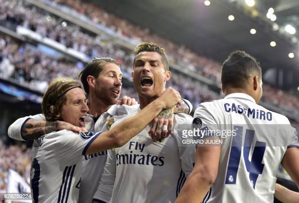 Real Madrid's Portuguese forward Cristiano Ronaldo celebrates with Real Madrid's Croatian midfielder Luka Modric and Real Madrid's defender Sergio...