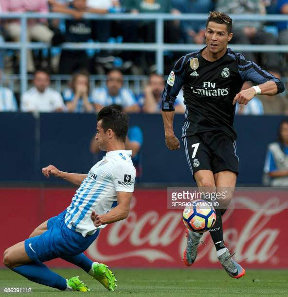 Real Madrid's Portuguese forward Cristiano Ronaldo controls the ball beside Malaga's defender Luis Hernandez during the Spanish league football match...